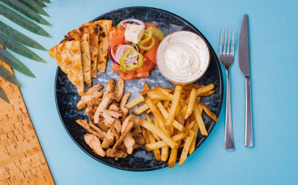 пилешко месо, пържени картофи, питка, салата и сос в чиния