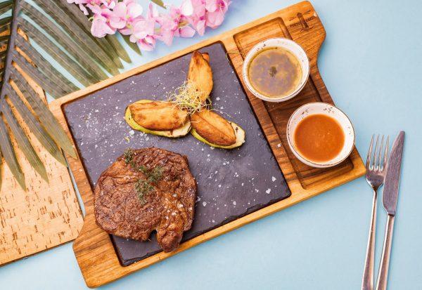телешки стек, сервиран на дъска с картофки и два соса в купички