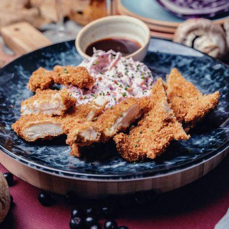 панирано пилешко със салата и сос в красива сива чиния