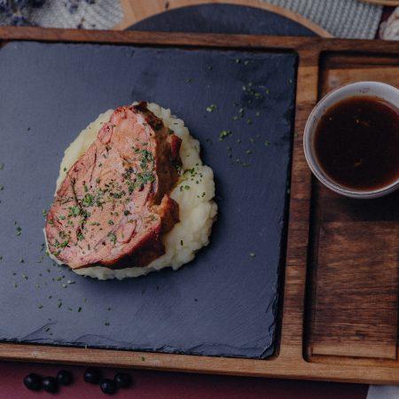 свински врат върху канапе от картофено пюре сервиран на дъска от черна слюда със сос